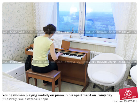 Купить «Young woman playing melody on piano in his apartment on  rainy day», фото № 25837461, снято 1 мая 2015 г. (c) Losevsky Pavel / Фотобанк Лори