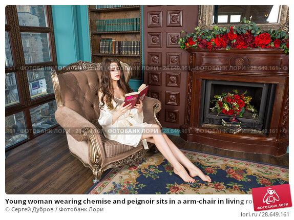 Купить «Young woman wearing chemise and peignoir sits in a arm-chair in living room and reads a book», фото № 28649161, снято 1 апреля 2018 г. (c) Сергей Дубров / Фотобанк Лори