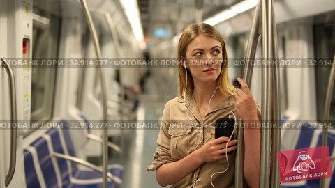 Купить «Young woman with a smartphone and headphones enters a subway car», видеоролик № 32914277, снято 31 марта 2019 г. (c) Яков Филимонов / Фотобанк Лори