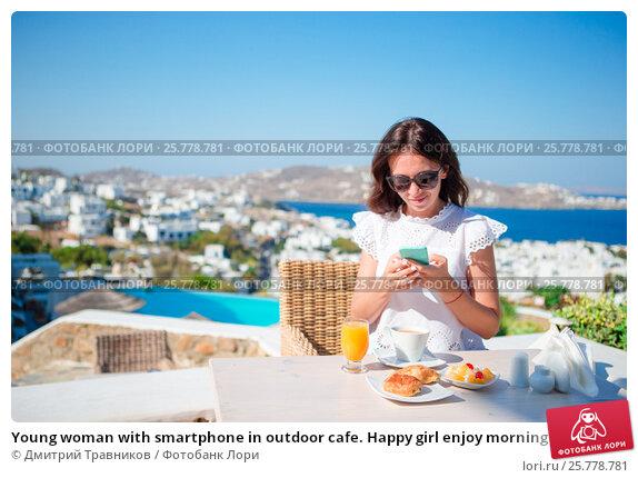 Купить «Young woman with smartphone in outdoor cafe. Happy girl enjoy morning time in cafe with beautiful view», фото № 25778781, снято 22 августа 2016 г. (c) Дмитрий Травников / Фотобанк Лори