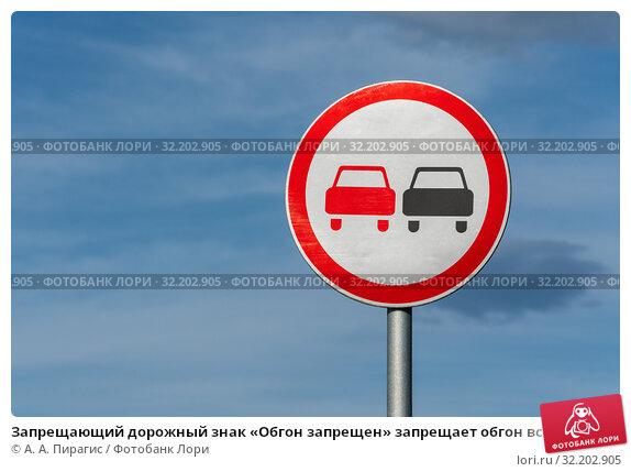 Запрещающий дорожный знак «Обгон запрещен» запрещает обгон всех транспортных средств на автодороге. Вид на знак на фоне синего неба и облаков в солнечную погоду. Стоковое фото, фотограф А. А. Пирагис / Фотобанк Лори