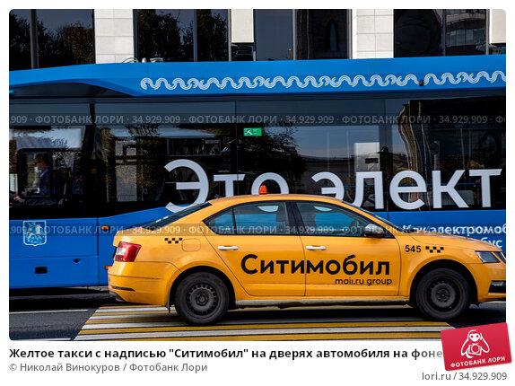 """Желтое такси с надписью """"Ситимобил"""" на дверях автомобиля на фоне электробуса в центре города Москвы, Россия. Редакционное фото, фотограф Николай Винокуров / Фотобанк Лори"""