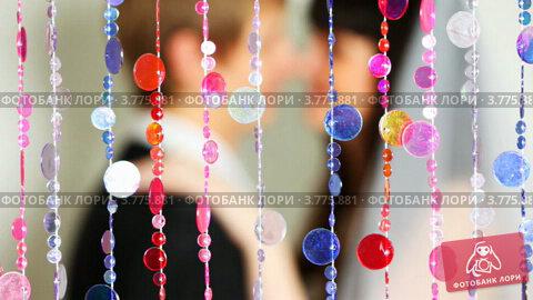 Купить «Жених и невеста целуются за расфокусированными занавесками из бисерных нитей», видеоролик № 3775881, снято 4 марта 2012 г. (c) Losevsky Pavel / Фотобанк Лори