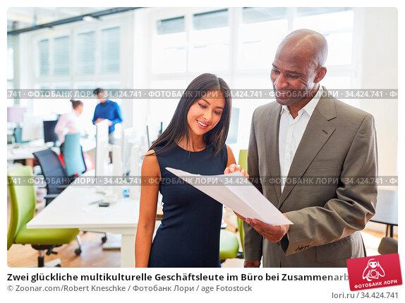 Zwei glückliche multikulturelle Geschäftsleute im Büro bei Zusammenarbeit... Стоковое фото, фотограф Zoonar.com/Robert Kneschke / age Fotostock / Фотобанк Лори